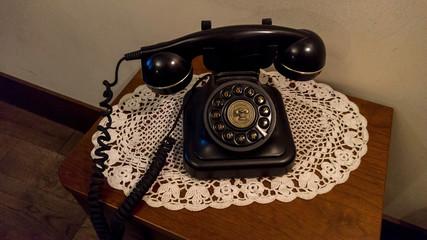 Black retro landline phone on wooden table