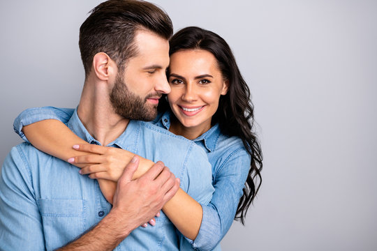 Love affair. Portrait of charming couple of millennial cheerful positive placing hands around chest wavy curly hair wearing blue denim shirts isolated on grey background