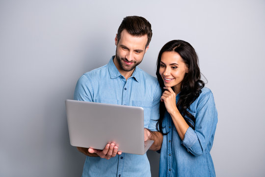 Portrait of charming inspired students using electronic devices watching videos browsing sites social networks isolated dressed in blue denim clothing on gray background