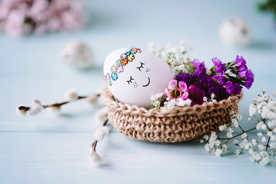 Schlafendes, süßes Osterei liegt im Osterkörbchen mit hübscher Blumendekoration