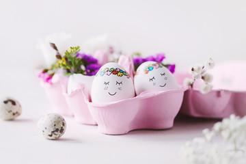 Süße Ostereier mit netten Gesichtern im rosa Eierkarton und Blumendekoration