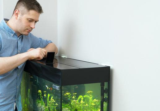 Handsome man feeding fishes in the aquarium.