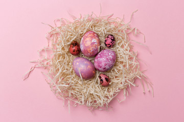 Easter eggs in nest on pink background. Easter texture