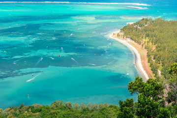 Beautiful view of a tropical beach with crystal clear water full of people windsurfing, from the mountain in le Le Morne Brabant, Mauritius
