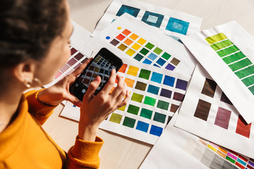 Cheerful artistic woman choosing paint color on a palette