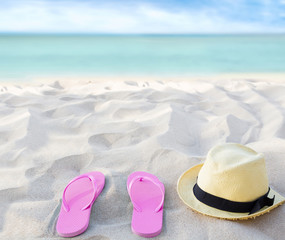 Beach summer holiday background. Flip flops and hat on sand near ocean. Summertime accessories on seaside. Tropical vacation and relax travel concept. Top view and copy space. Selective focus