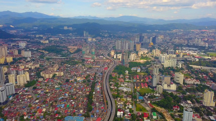 Aerial view of Kuala Lumpur Downtown, Malaysia and highways road. Financial district and business centers in smart urban city in Asia. Skyscraper and high-rise buildings at noon with blue sky.