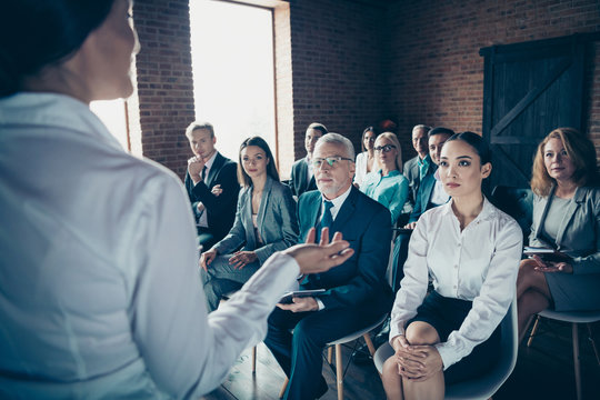 Crowd of nice serious stylish elegant specialists sharks sitting listening coacher speaker strategy salary profit plan economy corporate conference at industrial loft style interior work place station