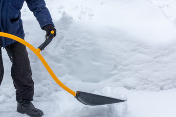 A man cleans snow in the yard with a shovel after a heavy snowfall