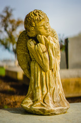 A aged yellow Angel grave statue on a grave. It was white at one time, and the alabaster turned yellow.