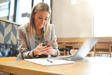 Saleswoman checking cellphone on business trip