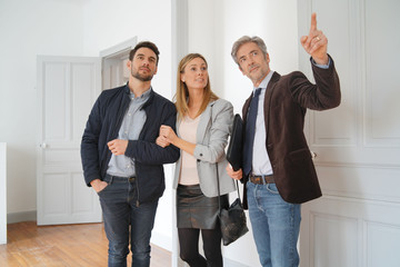 Couple with real-estate agent visiting light contemporary house