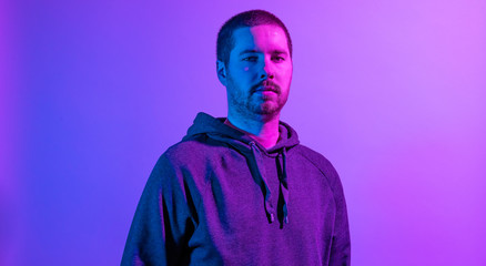 Serious unshaven man posing in purple studio light