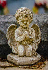 A aged white alabaster angelic angel statue on a grave praying. It is about 4 inches tall in height.