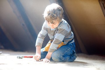 Little kid boy helping with toy tools on construction site. Funny child of 6 years having fun on building new family home. Kid with nails and hammer helping father to renovate old house.
