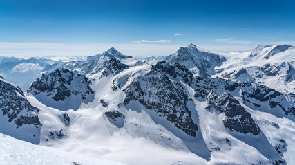 Switzerland, panorama view from Titlis mountain on Alps and mountains above white clouds