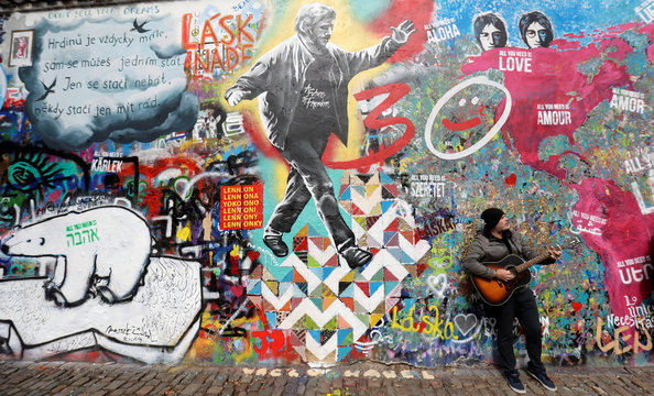 A man plays a guitar in front of the legendary graffiti-covered John Lennon Wall in Prague