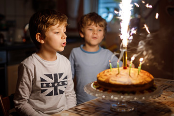 Two beautiful kids, little preschool boys celebrating birthday and blowing candles on homemade baked cake, indoor. Birthday party for siblings children. Happy twins about gifts and fireworks on tarte.