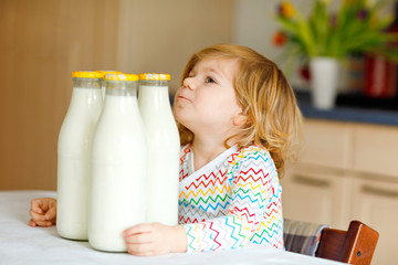 Adorable toddler girl drinking cow milk for breakfast. Cute baby daughter with lots of bottles. Healthy child having milk as health calcium source. Kid at home or nursery in the morning.