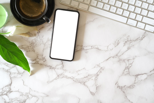 Mock up blank screen mobile phone on marble office desk