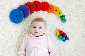 Cute adorable newborn baby playing with colorful wooden rattle toy ball on white background. New born child, little girl looking ath the camera. Family, new life, childhood, beginning concept.