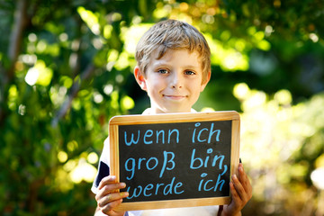 Happy little kid boy with chalk desk in hands. Healthy adorable child outdoors On desk When I grow up I want to be in German with dream profession