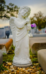 A white winged alabaster grave statue between two graves.  The expression on the face is of peace, and also tranquility.