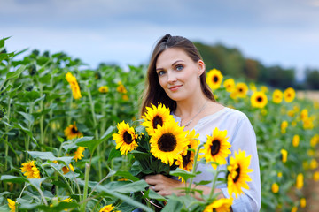 Beautiful young woman on sunflower field with bouquet flowers. Happy girl on summer sunset day.