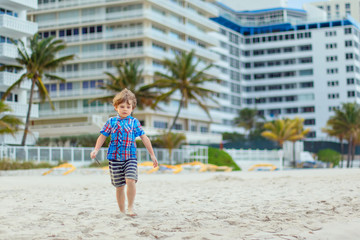 Portrait of happy little kid boy on the beach of ocean. Funny cute child making vacations and enjoying summer. Healthy boy on the beach of Miami USA on stormy windy day.