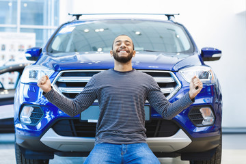 Happy young African man buying a new car - fototapety na wymiar