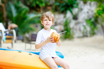 Happy funny little preschool kid boy drinking coconut juice on ocean beach. child playing on family vacations on tropical island. summer, happiness, childhood concept.