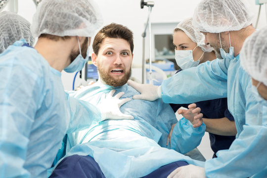 Group of surgeons holding scared male patient on surgery table