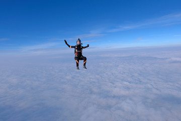Skydiving. Pretty girl is sitting above white clouds.