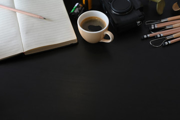 Creative workplace camera, coffee and note paper on black table with selective focus.