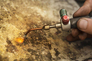 Professional jeweler repairman soldering jewelry with soldering torch