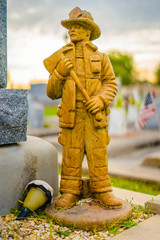 A aged alabaster firemen grave statue on a grave.  The alabaster has discolored from the elements. The firemen has the firemen axe, and in full uniform.