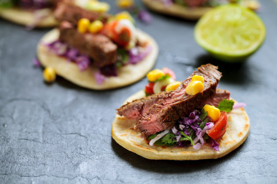 Beef steak tortillas with avocado, sweet corn, tomato salsa and red cabbage