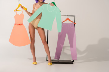 partial view of girl in underwear posing with colorful paper clothes on white