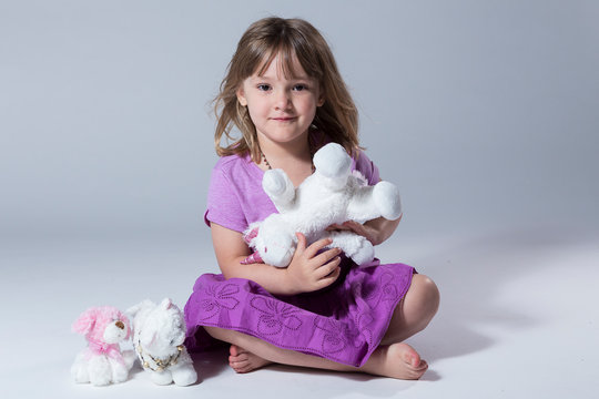 Little girl in pale purple top and purple skirt sitting holding a stuffed plush unicorn