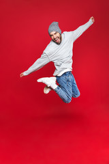 Full length photo of energetic man smiling and jumping isolated over red background