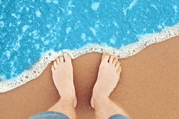 Feet beach, sea background. Male feet in sand, top view