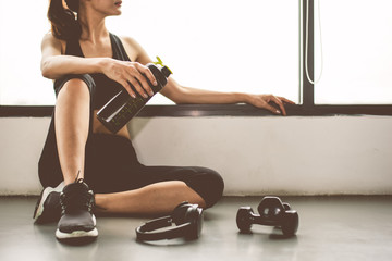 Woman with dumbbell and device exercise lifestyle workout in gym fitness breaking relax after sport training with protein shake bottle background. Healthy lifestyle bodybuilding and athlete muscles