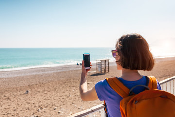 A girl takes a selfie on the beach.