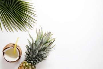 Summer mood concept. Tropical background with ripe organic pinapple with leafy crown, cracked coconut with milk and straw, sugar palm leaf. Flat lay, top view, copy space, isolated.