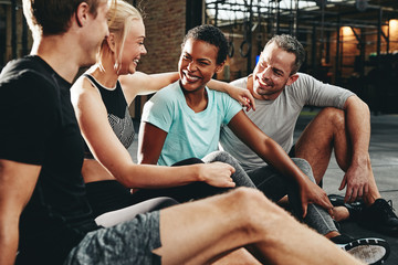 Smiling group of friends talking together after a gym workout
