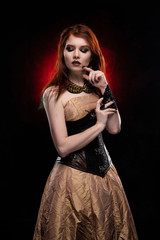 A beautiful thoughtful redhead cosplay girl wearing a Victorian-style steampunk dress and corset. Portrait. Black and red background.