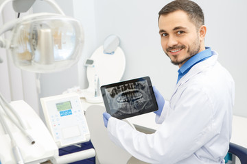 Professional male dentist using a digital tablet at work
