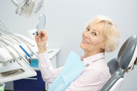 Happy senior woman at the dental clinic