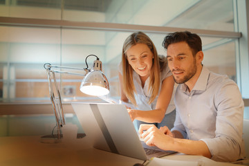 Male and female coworkers discussing ideas in modern office