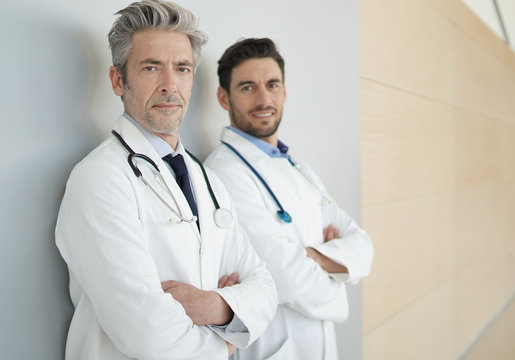 Male doctors looking at camera in hospital corridor